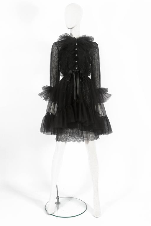 Exquisite and rare Yves Saint Laurent cocktail dress, circa 1980. The dress features two layers of lace, tulle overlayer with ruffled skirt, cuffs and collar, rhinestone buttons, silk bow fastening and attachable silk slip.