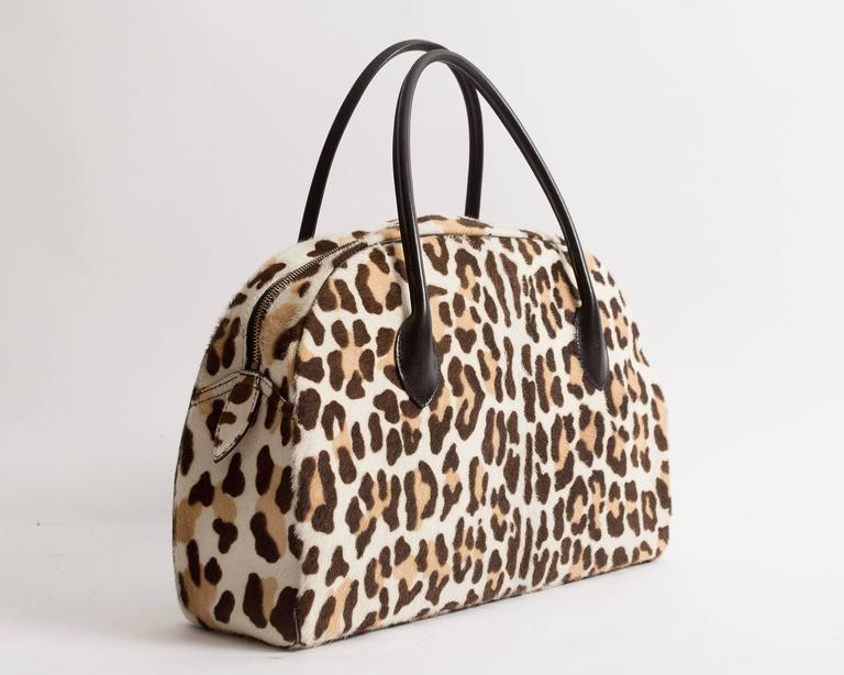Alaia large pony hair leopard print tote bag with black leather handles, gold metal zip closure, and black leather interior.
