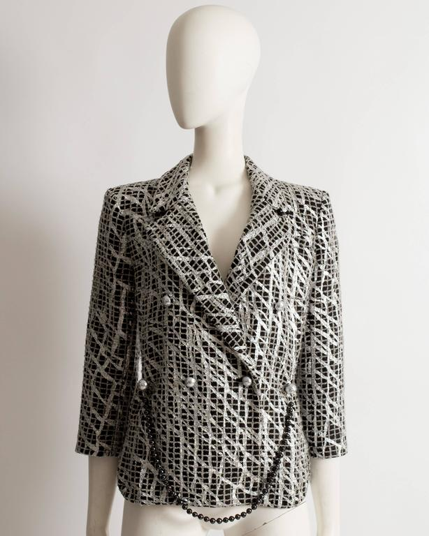 Limited edition Chanel evening jacket constructed in a black and gray checked tweed decorated with metallic silver paint in a graffiti style. Removable beaded chain belt, large silver button closures throughout and silk lining.