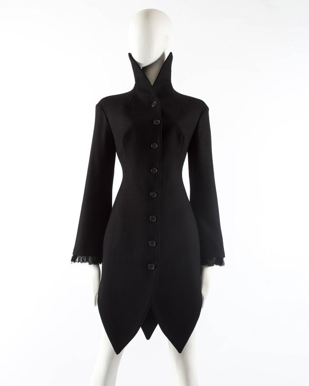 Alexander McQueen black wool evening coat, autumn-winter 2008. Eight button closure at the front,  high standing pointed collar with internal boning, flared sleeves with frayed trim and black silk lining.
