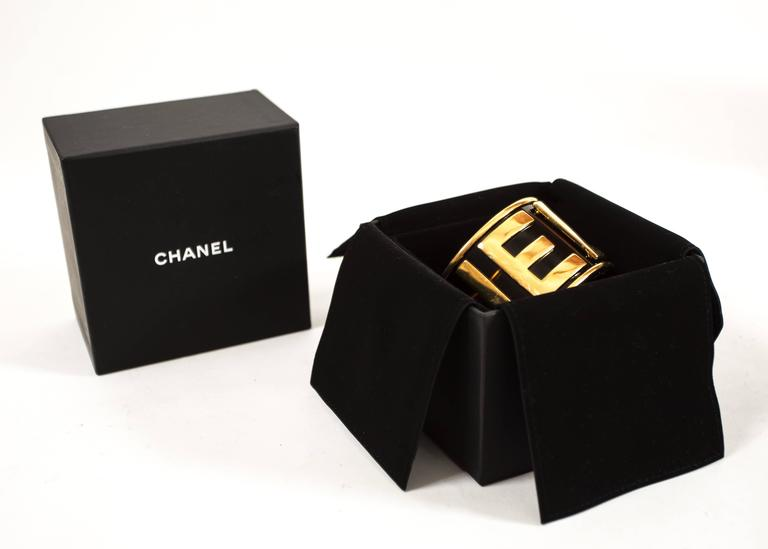 Chanel 1988 black and gold bangle bracelet featuring the 'CHANEL' logo in gold metal.