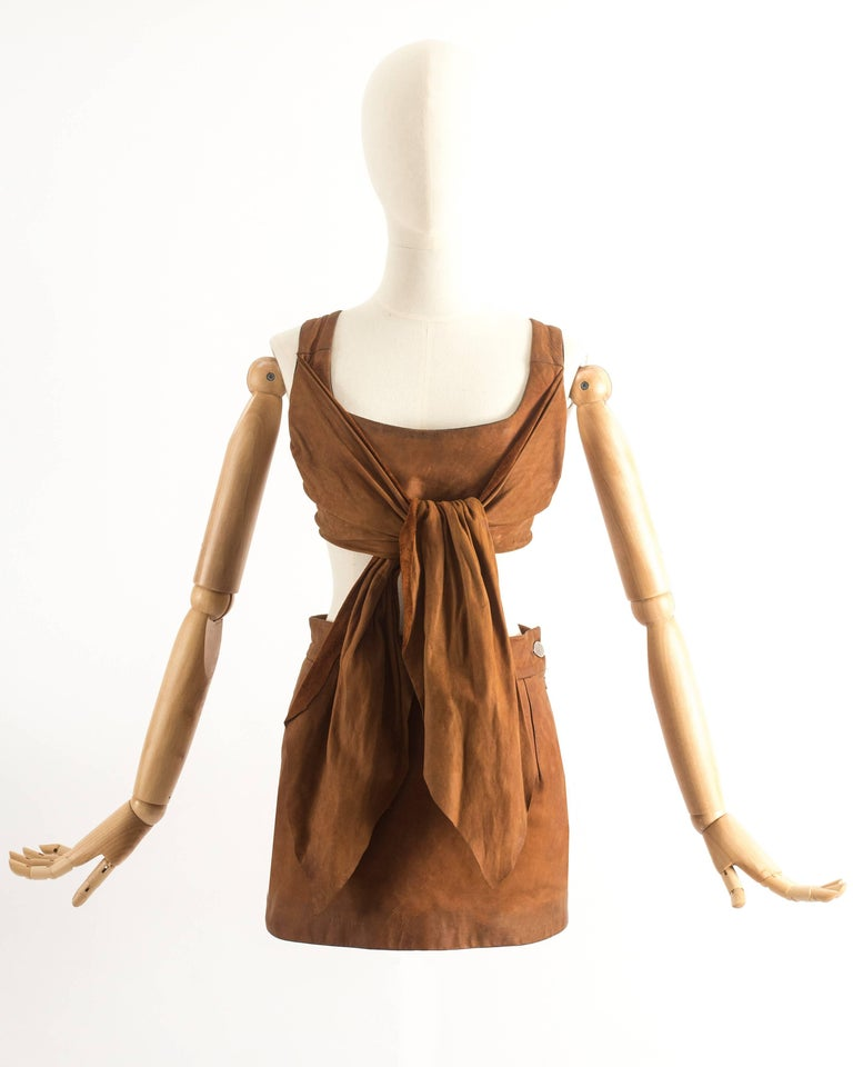 Vivienne Westwood Spring-Summer 1992 brown leather corset with boning, zip fastening and two long tie-up sashes at the front. High waisted mini skirt with slit at the rear.