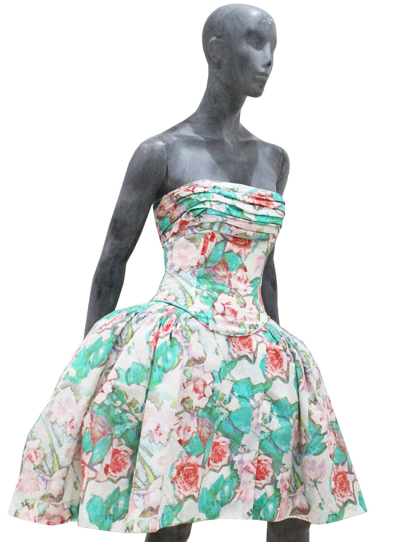 Designed by Karl Lagerfeld this beautiful cocktail dress in the spirit of Marie Antoinette is definitely a show piece. The dress features an abstract painted floral print, a corseted bodice and a super wide pannier skirt (these skirts were