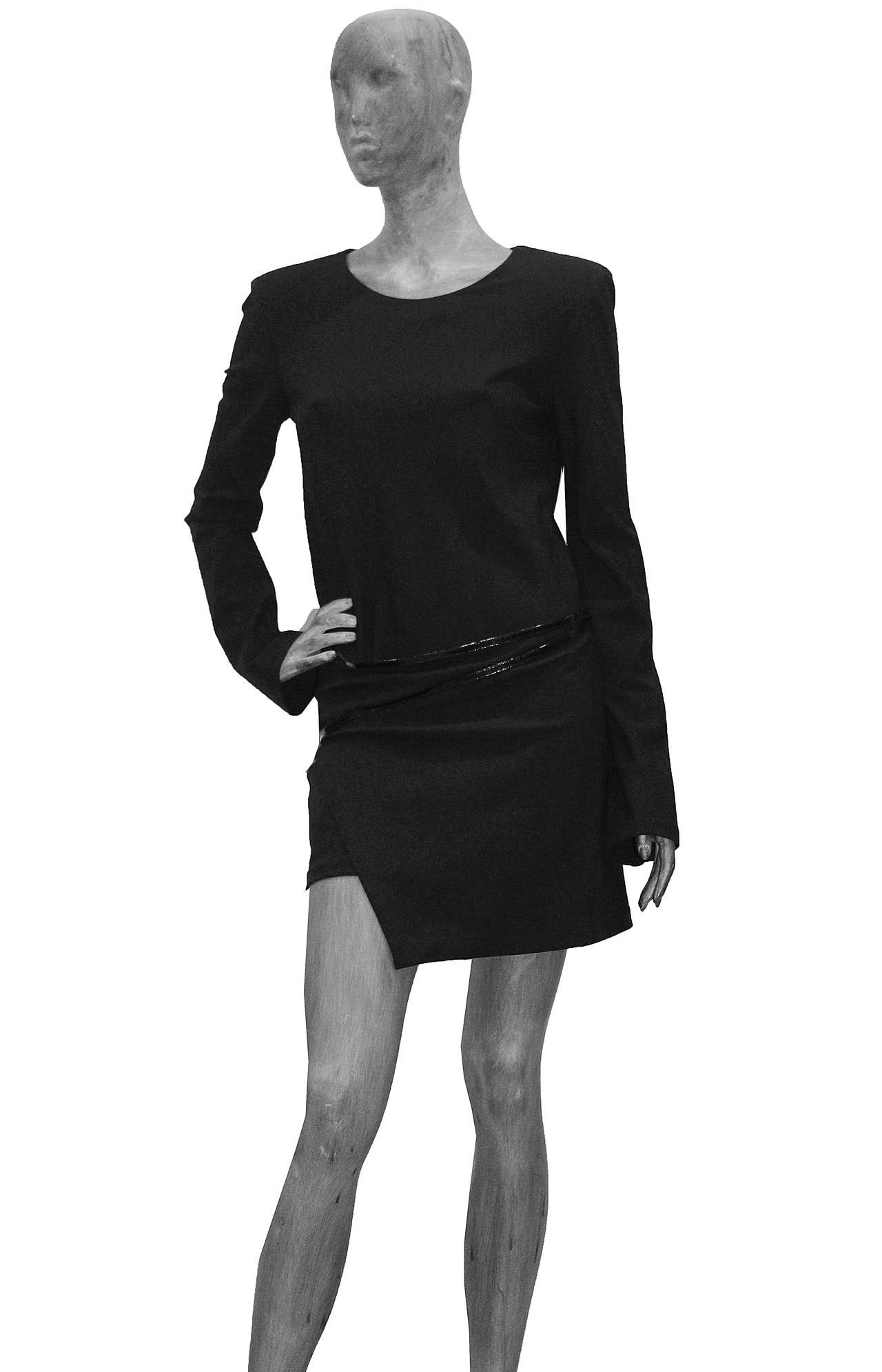 A fine and rare Gucci black mini dress designed by Tom Ford. The dress was first seen on the Milan catwalk for the famous Autumn/Winter 1997 show which defined the 90s.  This dress features long slim sleeves, a structured shoulder held by shoulder