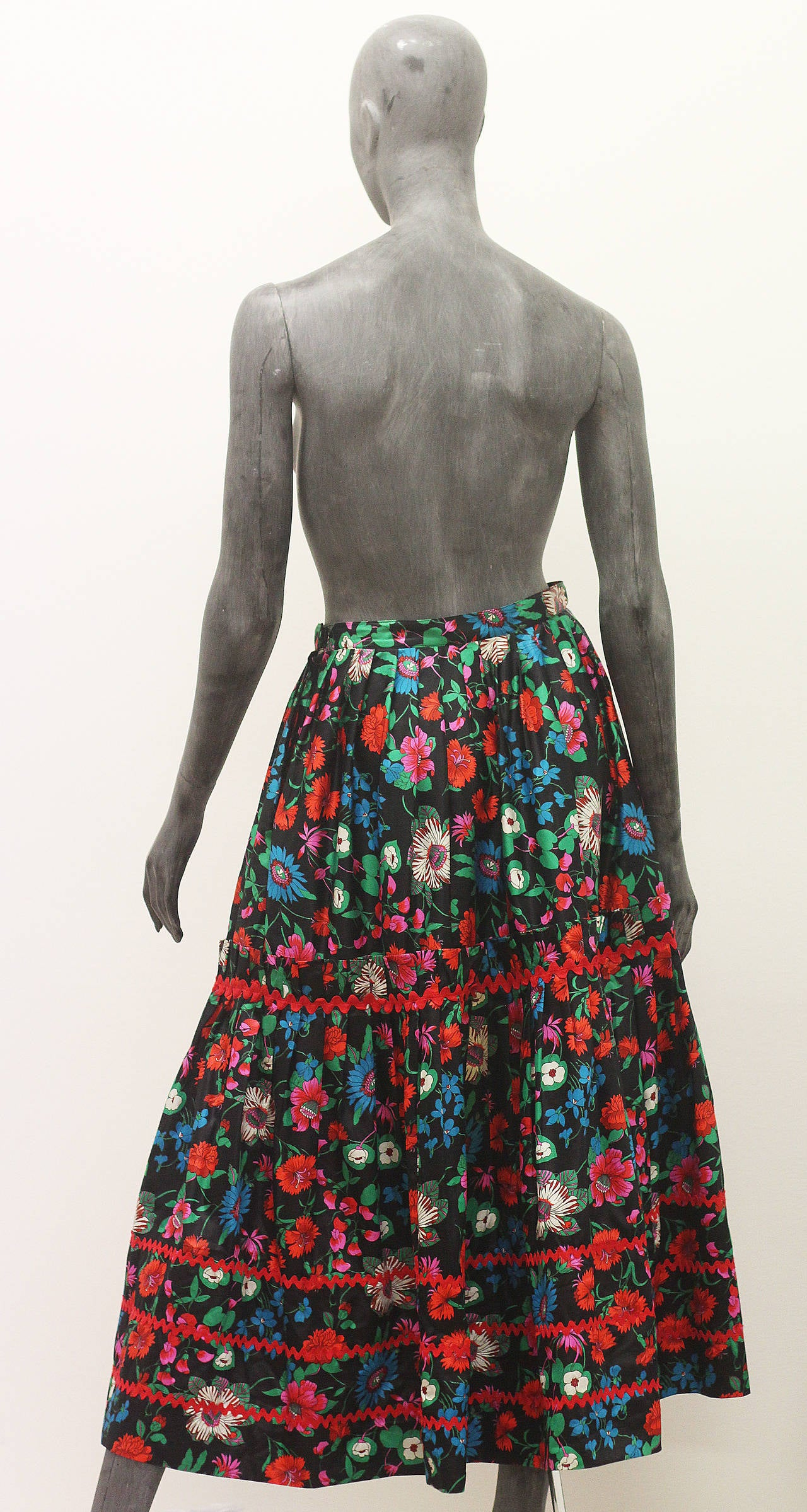 A beautiful pleated gypsy skirt by Yves Saint Laurent from the 1970s, the skirt features a vibrant floral illustrated pattern on a black ground, two side pockets and red trimming.   Waist: 28 inches - 71.12 centimetres Length: 35 inches - 88.9