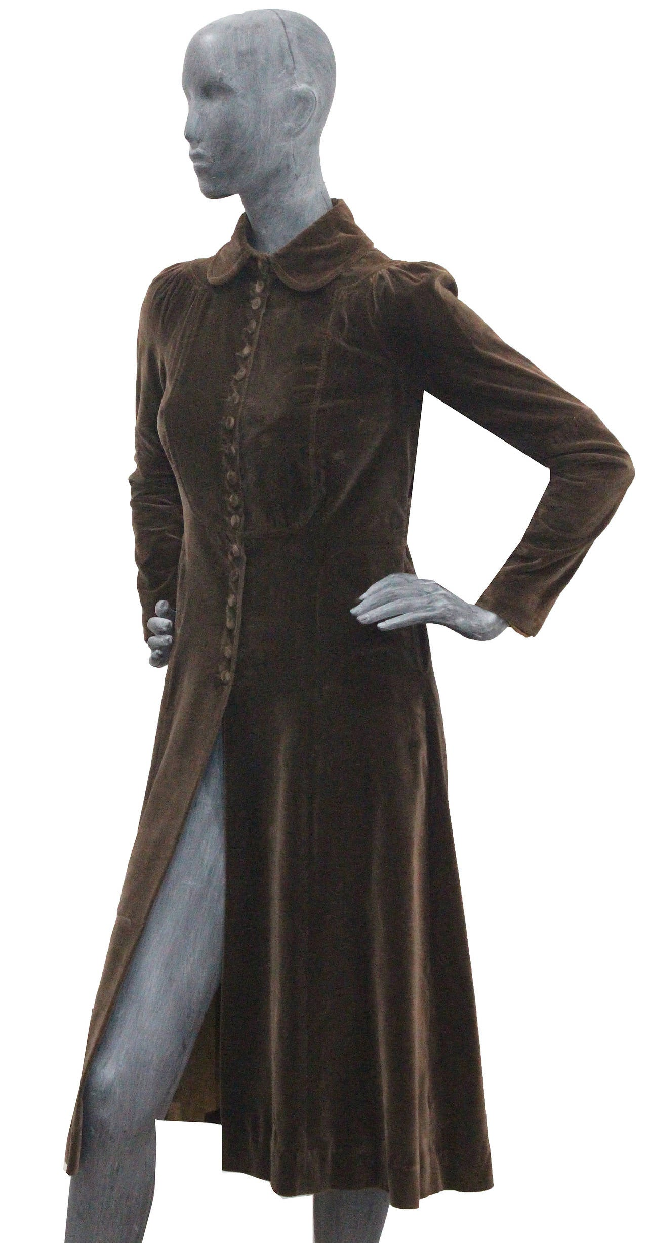 A fine and rare Ossie Clark brown velvet coat made exclusively for Bonwit Teller (New York, U.S.A.). The coat has a pleated back with a hanging belt, pleated fitted sleeves, two hidden open front pockets and velvet fabric buttons running through the