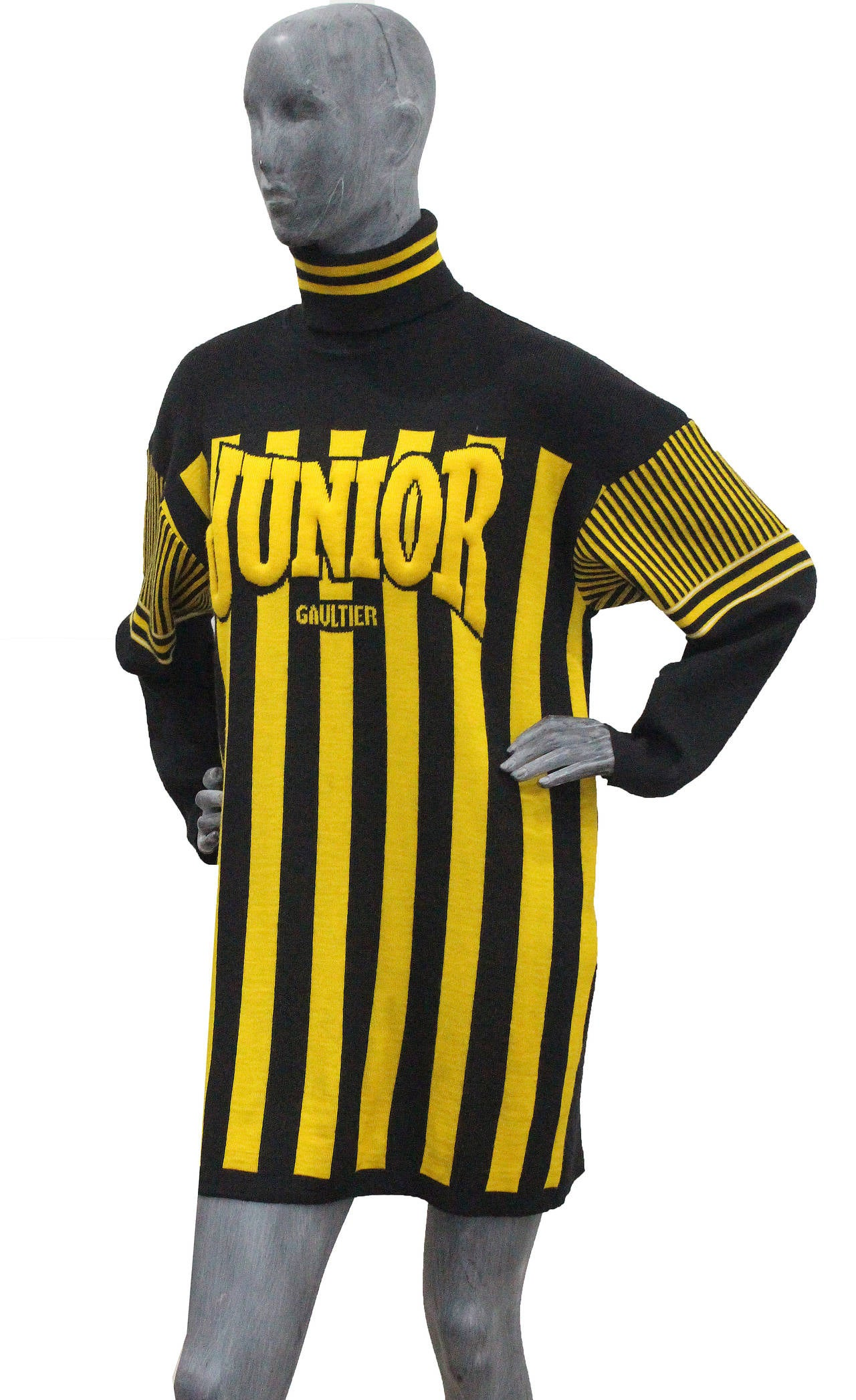 A rare knitted football sweater dress by Jean Paul Gaultier. The dress has yellow and black stripes, turtle neck and padded 'JUNIOR GAULTIER' on the bust.  Medium