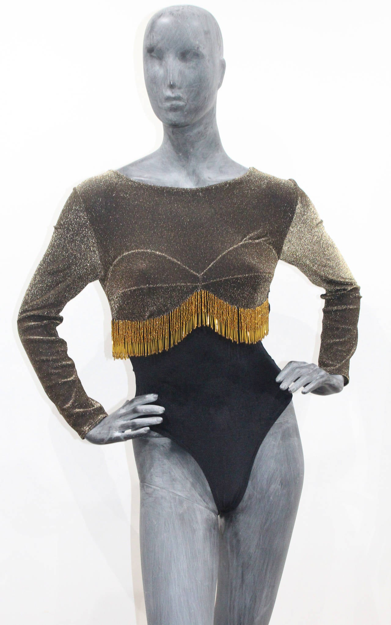 A great show girl leotard from the 1980s made of lurex and black stretch velvet. The leotard has a built in bra and gold beaded tassels all the way around underneath the bust.  Zip side closure. 