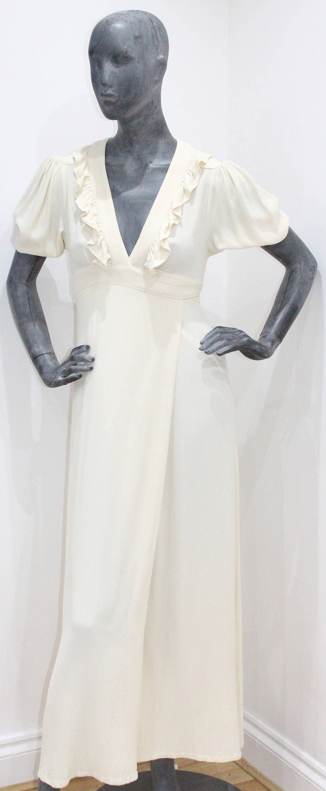 A beautiful ivory wrap dress by Ossie Clark. This design is timeless and chic. The dress has a v-neck plunge with a ruffled trim, a wrap design which ties as a bow to the rear, a central leg slit, structured 1940s inspired shoulder and draped puff