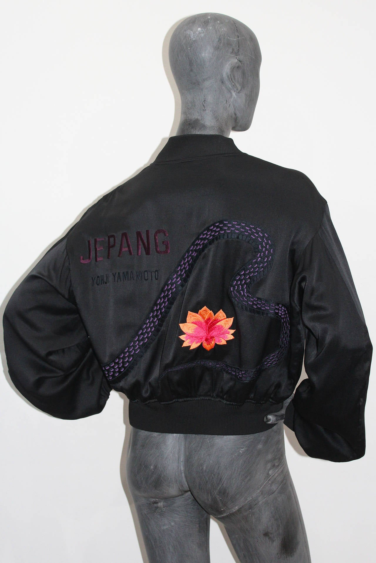 An embroidered black silk bomber jacket by Yohji Yamamoto. 