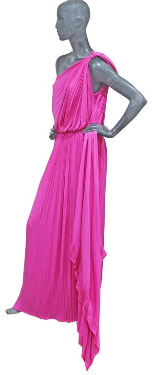 An exceptional Grecian inspired asymmetric hot pink pleated evening dress. The dress has a large bow which hangs off the shoulder with a long pleated train.    100% Silk  Size Shoulder to shoulder - 15