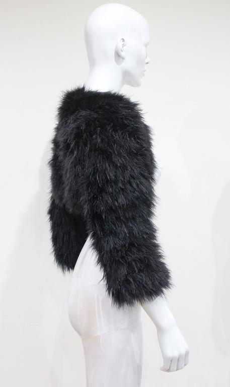 An Alexander McQueen black marabou fur bolero jacket from the year 2005. The jacket leaves the front bear and covers the back and arms. 
