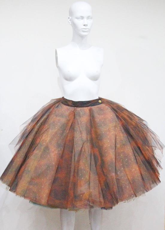 A museum worthy Vivienne Westwood tulle skirt from the year 1993. The skirt has various layers of netted tulle in a ray of colours and prints. The skirt lowers at the front gradually getting shorter towards the rear leaving the layers fully exposed