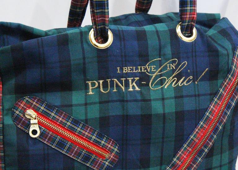 A Moschino large tote bag and matching purse from the early 1990s. The bag is in a mix match tartan print and features two top handles, large safety-pin zipper, and a gold embroidered 'I BELIEVE IN PUNK CHIC!' motif.
