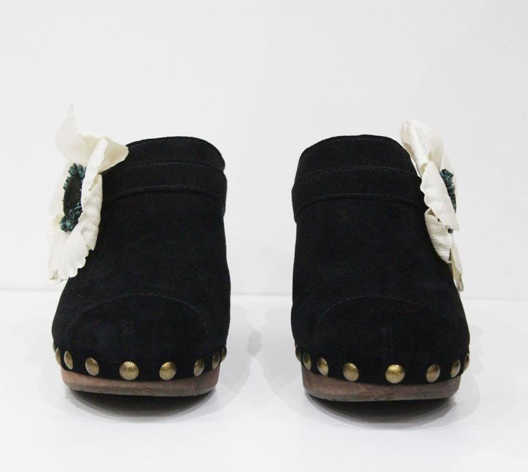 A pair of Chanel wooden platform clogs from the Spring/Summer 2010 collection. The clogs features bronze studs, black suede and a fabric flower appliqué. 
