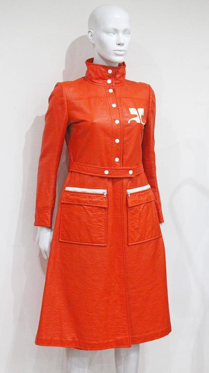 A Courreges coat dress from the year 1970 in orange vinyl fabric. The coat dress features stand collar, matching belt; white dot-button at centre-front and large Courreges logo on left breast. 