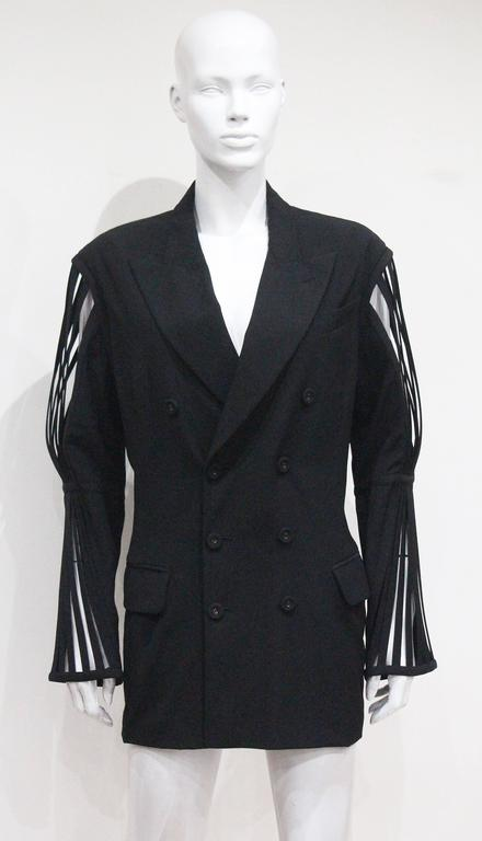 Fine and rare Jean Paul Gaultier double breasted black woollen blazer jacket, circa 1989. The blazer jacket has extraordinary caged boned sleeves. The beauty about this piece is that we believe it could be worn by a woman styled as a mini dress or