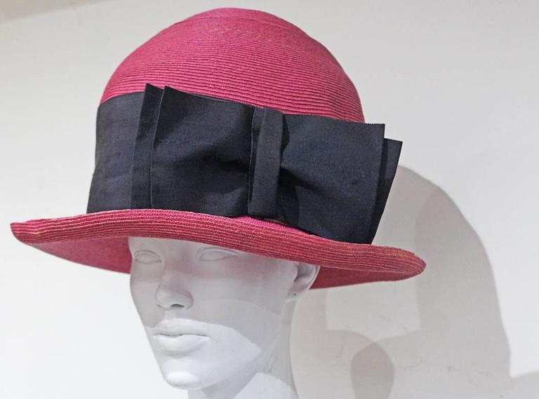 A rare oversized Vivienne Westwood straw hat by Vivienne Westwood. The hat has been painted in shocking pink and features a huge black fabric band and bow.