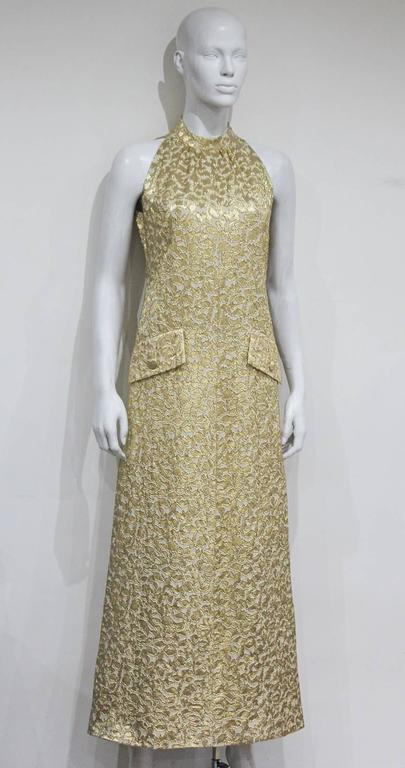 An exquisite 1968 evening dress by the legendary French fashion house Jean Patou. The dress is a classic late 60s a-line finishing just above the ankles, it features two front imitation pockets for decorative purpose, ivory silk lining, a side metal