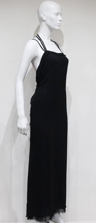 A Yves Saint Laurent silk chiffon black evening dress from the Autumn/Winter 2001 season, designed by Tom Ford. The dress features three halter neck straps and intentional frayed edges throughout. The seam closes in the centre at the rear of the