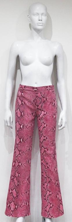 A pair of bell bottom pants by Tom Ford for Gucci from the Spring/Summer 2000 runway collection. The pants are in a hot pink python print and 100% cotton. 