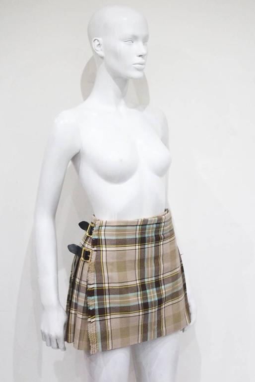 A rare Vivienne Westwood mini pleated mini skirt in the style of a Scottish kilt. The skirt features three gold Baroque style buckles and is made of 100% Scottish tartan wool. Kate Moss wore an identical skirt in a different colour for the Vivienne
