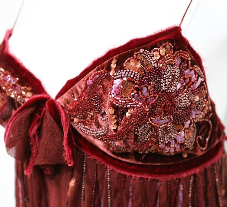 A beautiful Christian Dior mini dress from the Autumn/Winter 2005 collection designed by John Galliano. The dress is of a red draped silk chiffon and features a velvet bust embellished with glass beads.   Pristine Condition