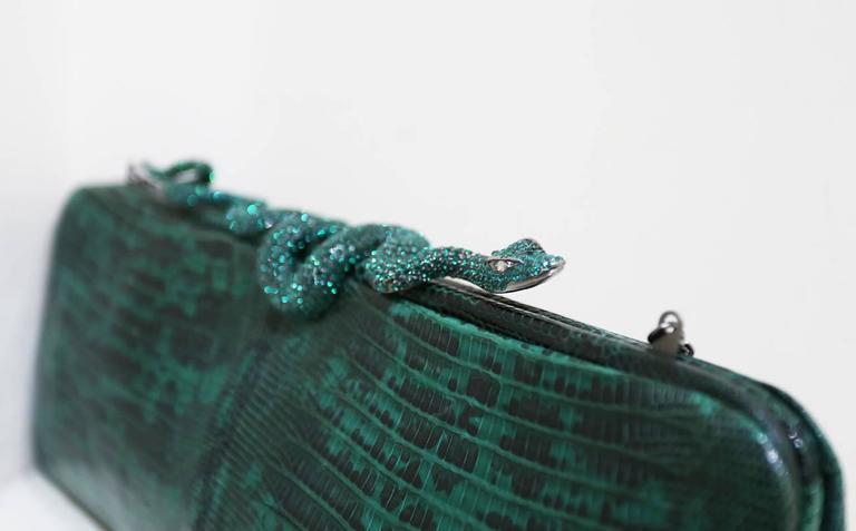Fine and rare Valentino dark green genuine lizard skin evening bag/clutch with encrusted crystal snake closure, silk satin black interior and optional metal shoulder chain which can be put inside of the bag to be worn as a clutch.