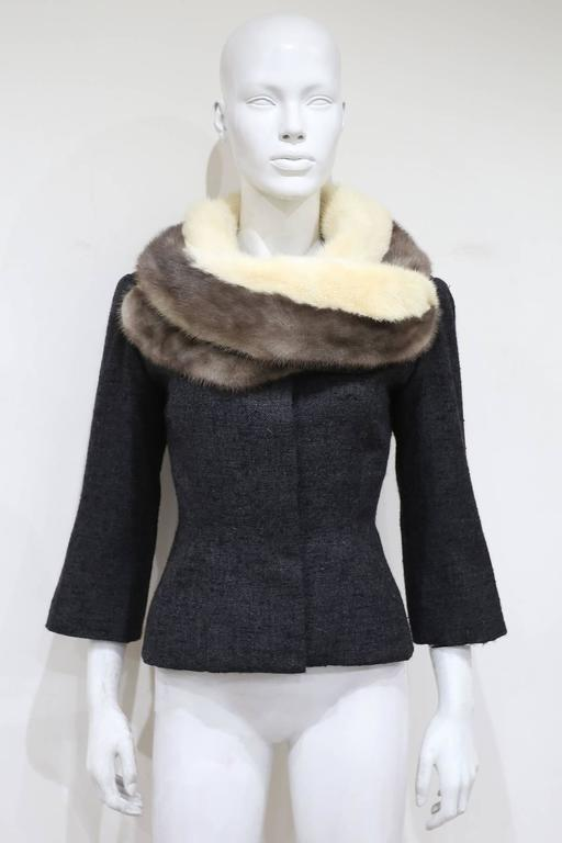 Jeanne Lanvin charcoal grey woollen jacket, circa 1950s. The jacket is exquisitely cut and features a unique wrap around collar appearing as a scarf. The coat also comes with a attachable mink fur collar which is fastened with hooks and snap