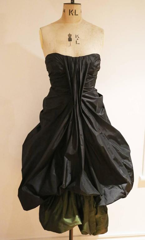 Extremely important and rare Alexander McQueen strapless silk taffeta evening dress from the witches collection, Autumn-Winter 2007. The dress features beautiful pleating throughout with an amazing ballon skirt and petrol green underskirt. There is