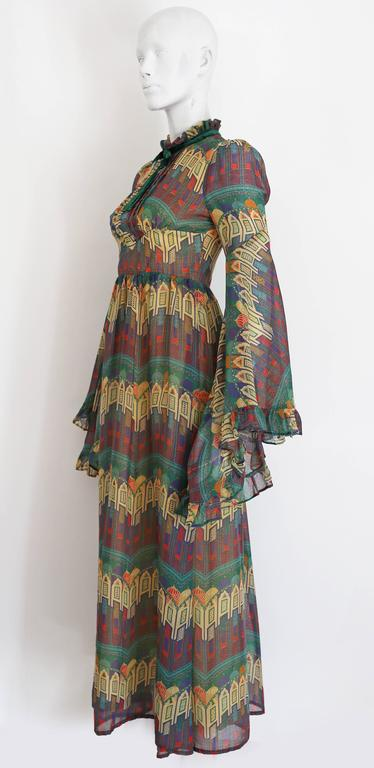 A beautiful novelty print voile summer dress by Samuel Sherman, the dress features exaggerated fluted sleeves and a high ruffled neck with decorative velvet bow. 