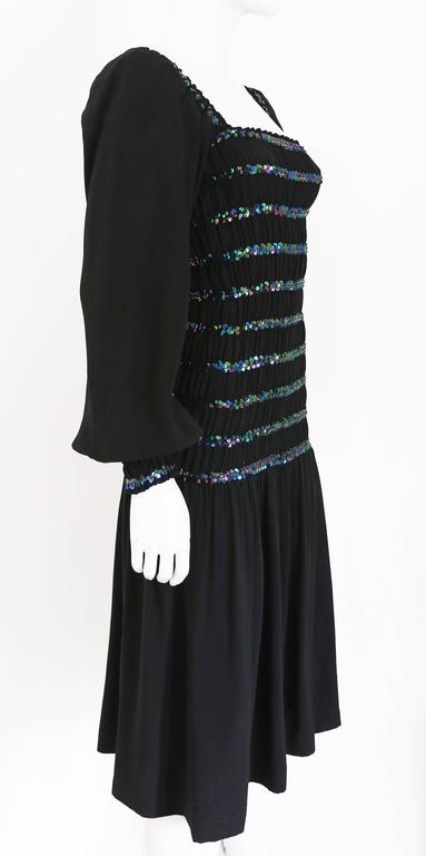 A Yves Saint Laurent party dress, circa 1976-77. The dress is smocked from shoulders to hips, has a square neckline, sequin embellishment and ruffled cuffs. 