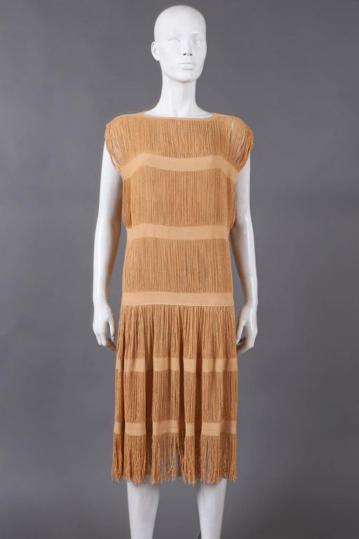 A beautiful linen flapper dress from the 1920s. The dress features 6 lien bands, fringed hem, high side slits and drop waist.  size small
