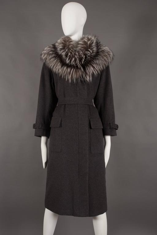 A Yves Saint Laurent charcoal grey cashmere fall coat, circa 1990.   Exaggerated arctic fox fur collar, hidden button closures on front opening, matching double button belt, two front flap pockets and black satin quilted lining.