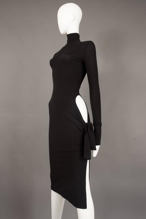 An iconic and rare Dolce & Gabbana bodycon evening dress from the spring summer 2001 collection. Black spandex-like stretch fabric, turtleneck, long fitted sleeves, invisible zip closure, high leg slit and circular cut on the lower hip with tie-up