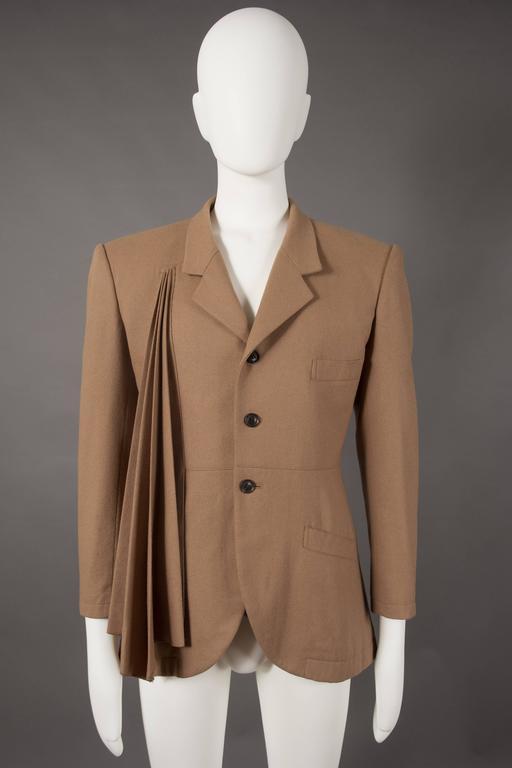 A rare and early Yohji Yamamoto men's blazer jacket, circa 1984-87. Internal waist belt, three button closure, and asymmetric pleated fabric on the chest.