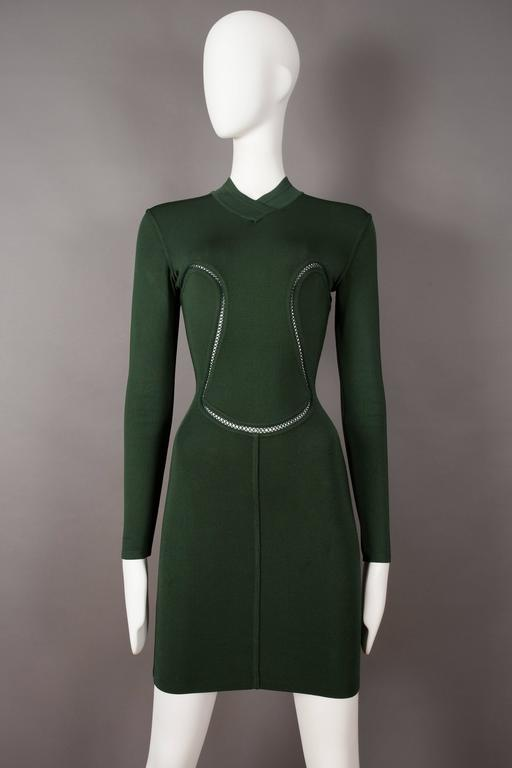 Alaia, autumn winter 1991.   High v-neck collar, super figure hugging stretch knit fabric, cut-outs with cross stitch throughout and invisible zip closure at rear.