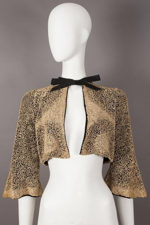 A beautiful 1930s bolero evening jacket with intricate ribbon embroidery throughout, cropped bell sleeves, silk chiffon lining and black bow fastening on the collar.