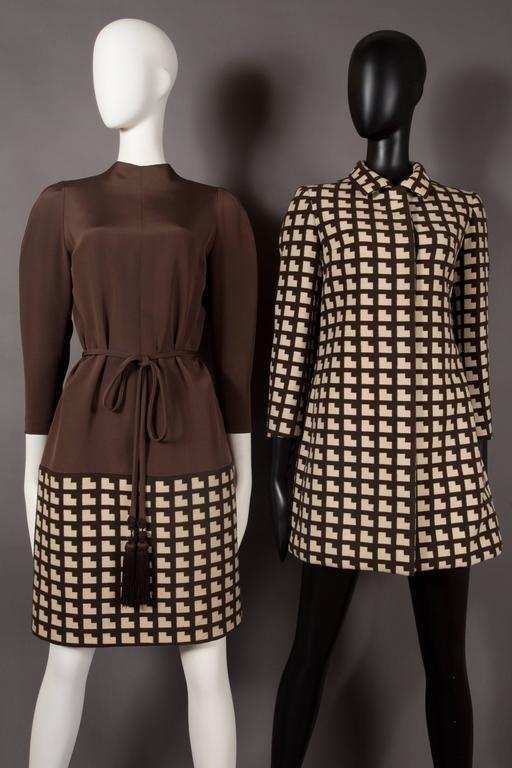 Exquisite and extremely rare Paul Daunay haute couture fall daytime ensemble, circa 1952-57. Brown and ivory wool in art deco style print throughout. The ensemble includes a tailored coat with hidden button closures, fitted sleeves and turn-over