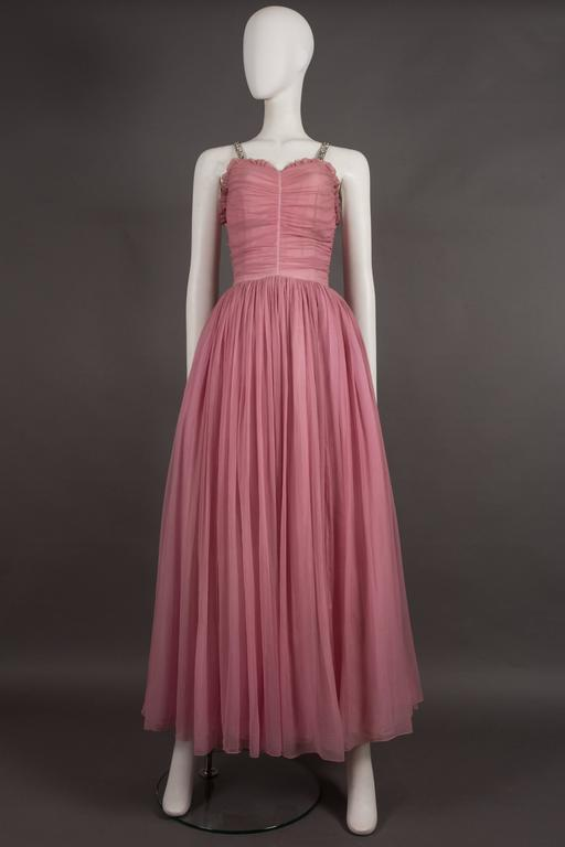 An exceptional couture 1940s evening gown in baby pink silk chiffon. The dress features rhinestone should straps, ruffled trim, ruched bust with original metal zipper and full pleated skirt with three interior layers of tulle, voile and silk
