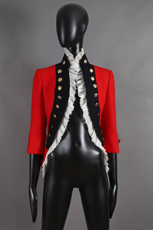 A rare Alexander McQueen matador-style jacket in red wool with pleated white cotton trim, decorative gold buttons throughout and hook-and-eye closure.   From the Autumn-Winter 'The girl who lived in a tree' 2008.