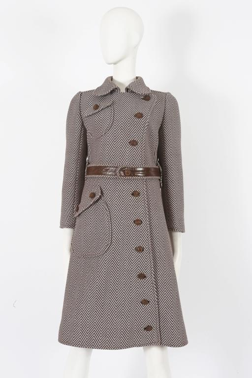 Courreges Haute Couture tailored coat in brown and ivory tweed, circa 1969. The coat features two front pockets, wooden buttons throughout, leather waist belt and silk lining.