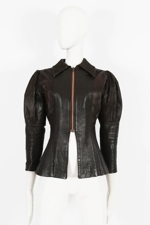 An early Ossie Clark 'Rocker' brown leather jacket, circa 1966, from his couture line. The jacket features pin-tucked bands on the upper sleeves, side panels and upper back, peplum style waist and metal zipper fastening.