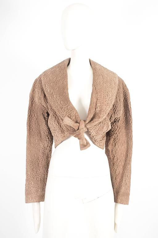 Alaia bolero jacket, constructed in a taupe embossed pigskin leather, silk lining and tie-up fastening on the waist.   Circa 1987  Size:  Shoulder to shoulder - 21
