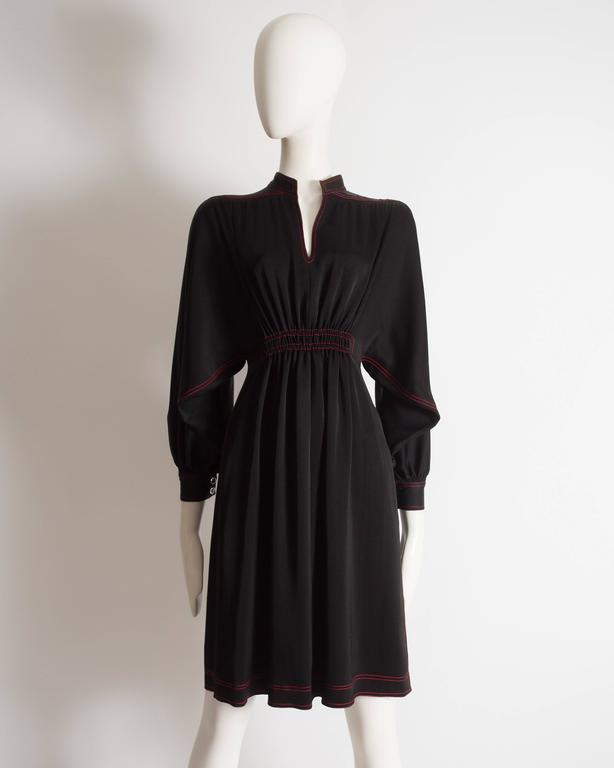 Jean Muir evening dress constructed in black silk with red contrast stitch, bishop sleeves, drawstring fastening around waist and gem buttons on the cuffs.  Circa 1972