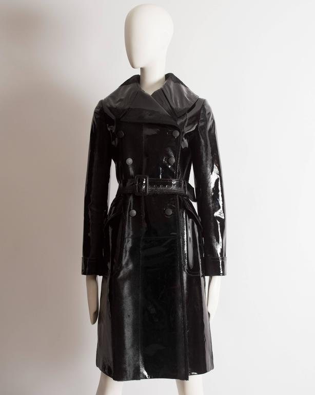 Rare Alaia trench coat constructed in pony hair from New Zealand, dyed black and partially varnished to give it a patent leather appearance. Double breasted, large structured collar and lapels, wooden button closures throughout, two diagonal front