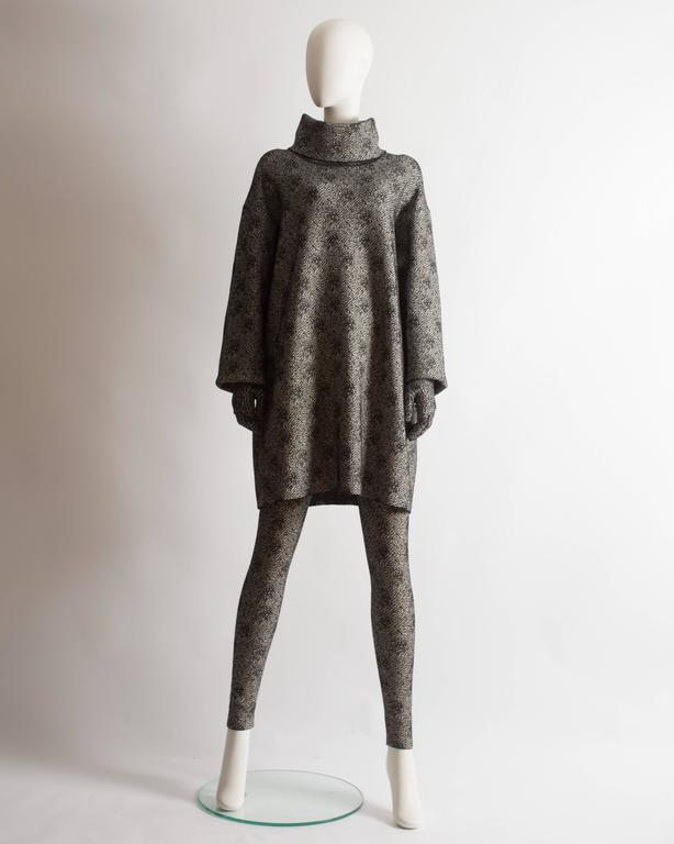 Alaia three piece ensemble. Oversized sweater dress with high turtle neck and two zip fastenings, high waist fitted leggings and matching gloves.