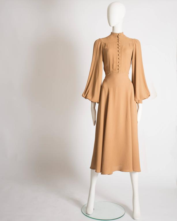 Ossie Clark mandarin collared dress constructed in caramel moss crepe. Button closures, pleated bishop sleeves, attached belt fastening at the rear, and fitted cuffs.