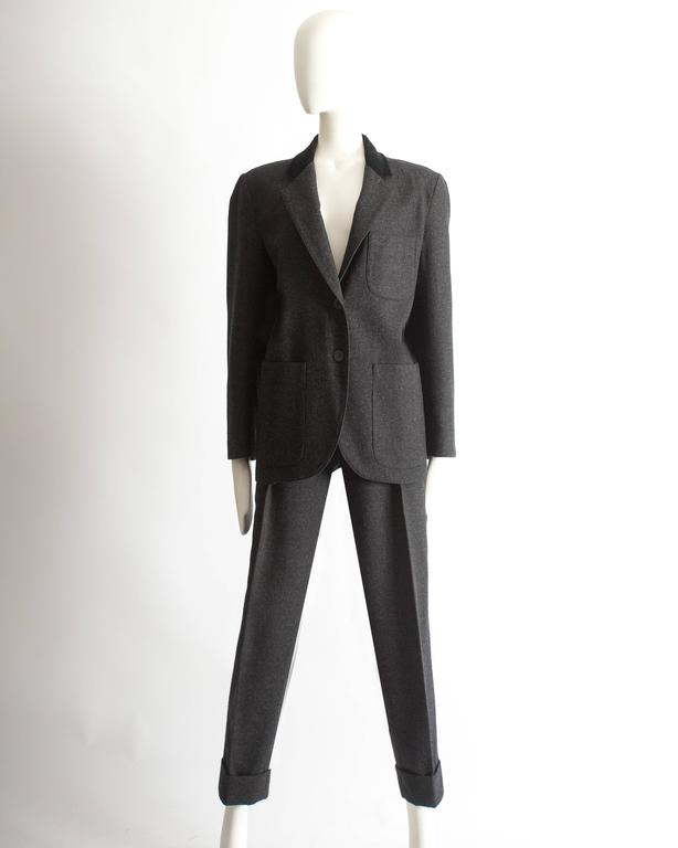 Alaia charcoal gray wool pantsuit. Boxy cut jacket with two button closure, silk lining, and black velvet collar. High Waist pleated pants with button closure and turn-over hem.   Autumn-Winter 1987