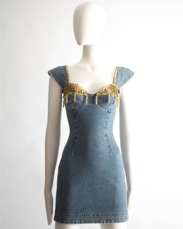 Katharine Hamnett denim mini dress. Sequin bust with chain tassels, capped sleeves, zip fastening at the back and two zip pockets.